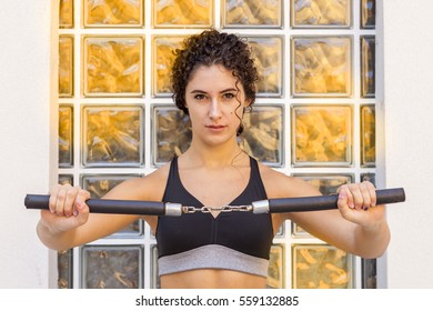 sporty woman training with the nunchaku japanese weapon