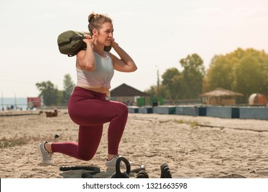 Sporty woman training with sand bag at the beach. Positive Fitness female working out in summer time. Place for text.