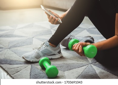 A sporty woman using smartphone during workout at home in the living room. Online personal trainer or on mobile phone.Sport and recreation concept.advice to stop coronavirus COVID-19 spreading.