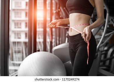 Sporty woman using waist tape line in fitness gym sport club training center near window with condominium background. Lifestyle of people workout exercise sport activity. Diet and weight loss theme.