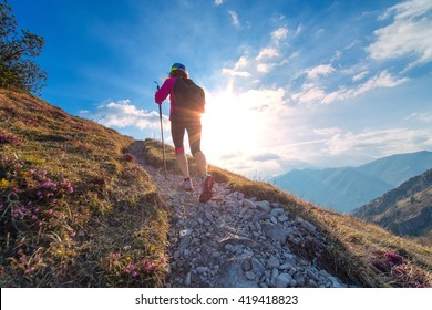 Sporty woman walking with Nordic walking in a mountain trail