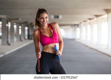 Sporty woman warming up with jump rope outdoors. Athletic Beautiful Woman Exercises with Jump / Skipping Rope.