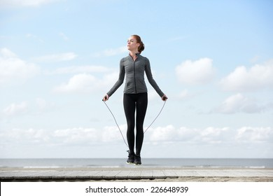 Sporty woman warming up with jump rope outdoors