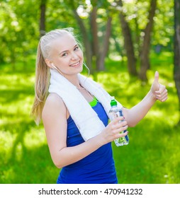 Sporty woman with a water bottle in hand showing thumbs up.