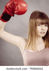 Sporty woman wearing red boxing gloves, fighting. Studio shot on grey, background.