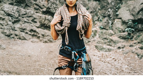 Sporty woman wearing in safety harness with climbing equipment holding rope on background of rock.