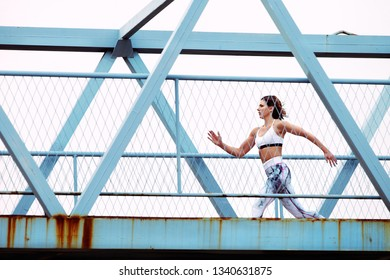 Sporty woman who is running in an urban setting over a bridge