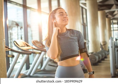 Sporty woman with wireless earbuds listening to music at gym