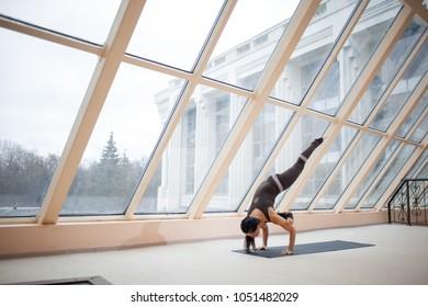 Sporty woman working out, doing arm balancing handstand yoga asana, One Legged Crane Pose, Half Crow Pose, eka pada galavasana of