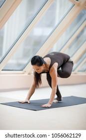 Sporty woman working out, doing arm balancing handstand yoga asana, One Legged Crane Pose, Half Crow Pose, eka pada galavasana in front of large window