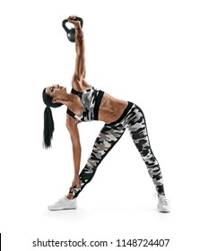 Sporty woman workout with kettlebell. Photo of latin woman in fashionable sportswear isolated on white background. Strength and motivation
