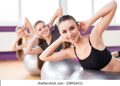 Sporty women are doing sit-ups on the exercise balls.