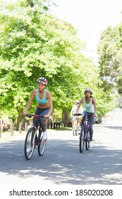 Sporty women riding bicycles on country road