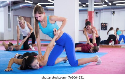 Sporty women are training self-defence moves in pairs in gym