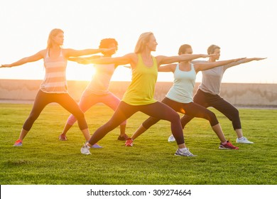 Sporty women warming up during fitness class in parkland