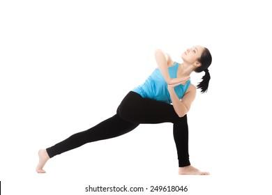 Sporty yoga girl exercises on white background in parivritta parshvakonasana (revolved side angle pose), palms in Namaste, isolated
