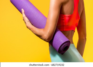 Sporty yoga girl with yoga mat wearing training clothes over vibrant background