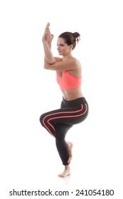 Sporty yoga girl on white background in garudasana (Eagle Pose)