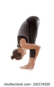 Sporty yoga girl on white background exercises, head to knees pose