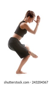 Sporty yoga girl on white background standing on one leg with palms folded in mudra