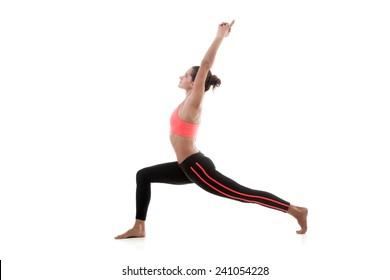 Sporty yoga girl stands on white background in virabhadrasana 1 (Warrior 1 Pose)