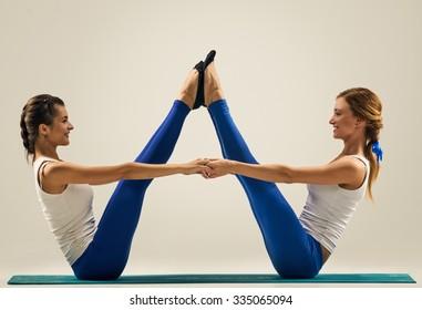 sporty yogi sisters doing fitness training. studio shot. pair, couple yoga
