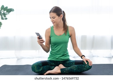 Sporty and young adult woman in sportswear sitting on fitness mat and using smartphone after training at home