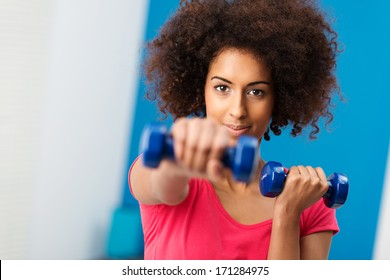 Sporty young African American woman working out with dumbbells in the gym extending her arm towards the camera with a determined expression