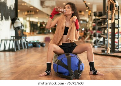 Sporty young Asian woman sitting on punching bag and drinking water