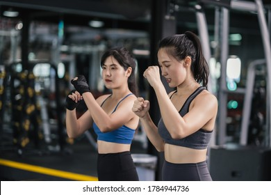 Sporty young asian women training boxer wearing strap on wrist with coach, Boxing practice sports for fight or workout with a partner at fitness gym healthy lifestyle and self defending concept.