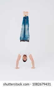 Sporty young barefoot casual man in jeans doing a handstand balancing on his hands as he smiles at the camera over a white background