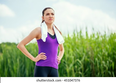 Sporty young beautiful woman standing before or after workout and running. Focused on exercises, on nature background. Sport. Recreation. With white towel on the neck.