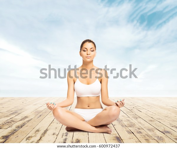 Sporty, young and beautiful woman in swimsuit meditating on a pier at summer. Sport and yoga concept.