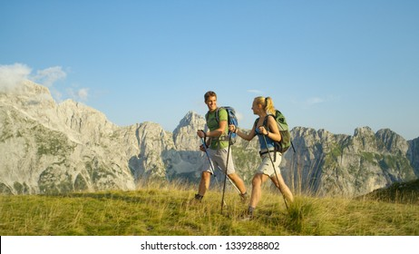 Sporty young Caucasian couple trekking high in the scenic mountains during their active spring holiday. Cheerful athletic man and woman enjoying the summer by hiking in the picturesque Slovenian Alps.