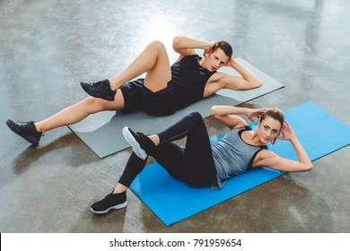 sporty young couple doing abs exercise in gym