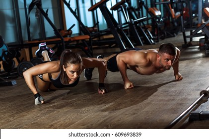Sporty young couple doing a push-ups at gym.