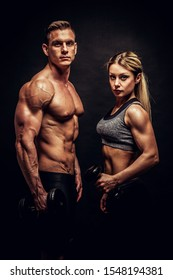 Sporty young couple with dumbbells on black background