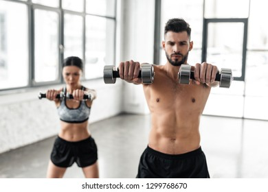 sporty young couple exercising with dumbbells in gym