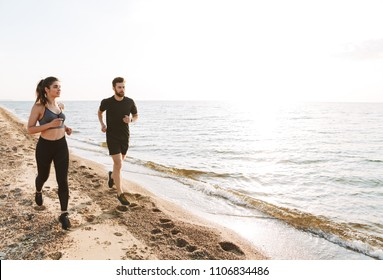 Sporty young couple jogging together on a beach during sunrise