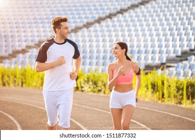 Sporty young couple running at the stadium