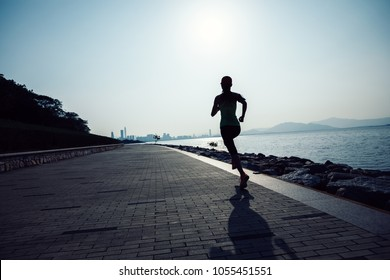 sporty young fitness woman running on sunrise coast trail