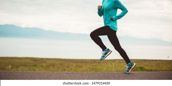 Sporty young fitness woman ultramarathon runner running on road