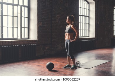 Sporty young girl with a ball in the loft
