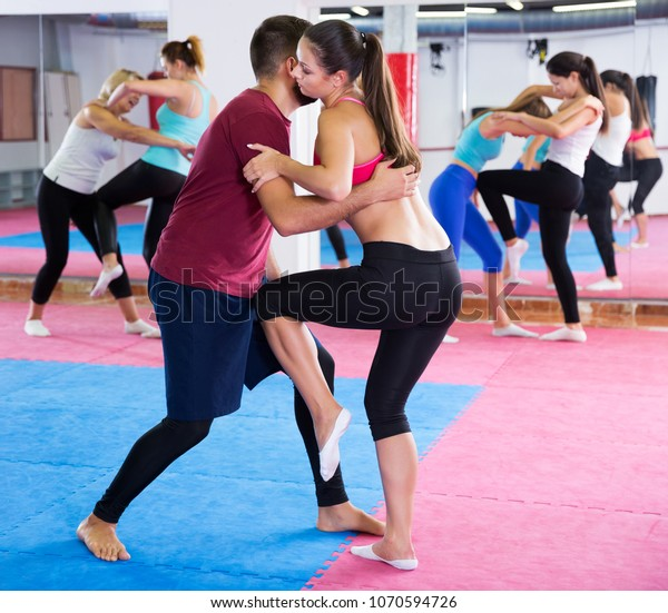 sporty young girl is doing self-defence moves with coach in sporty gym.