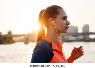 a sporty young girl jogging in the evening by the river