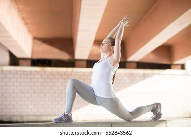 Sporty young girl practicing yoga, standing in Horse rider exercise, anjaneyasana pose, working out, wearing sportswear, outdoor full length, urban background