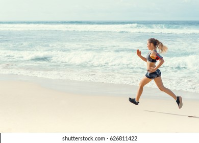 Sporty young girl running on beach