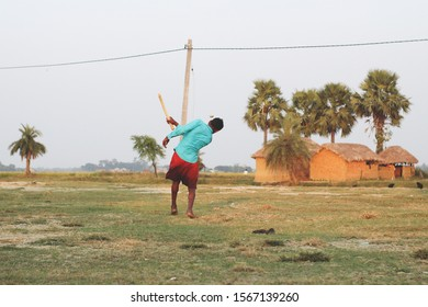 A sporty young guy playing indian popular game called Gilli Danda on the ground with his friends on a sunny morning.