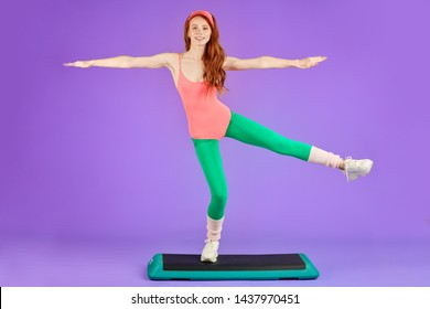 Sporty young joyful red-headed woman standing on one leg at step deck and holding balance, keeping hands wide apart, prefers indoor fitness training using gym equipment, wears green leggins and pink
