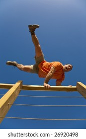 A sporty young male jumping over a wooden fence